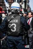 Détail du dos d'une police faisant face à des protestataires Photographie stock libre de droits