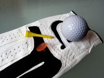 Détail en gros plan de boule de golf de gant de golf et de pièce en t jaune photos stock