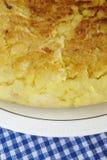 Détail espagnol d'omelette de pomme de terre sur un plat et une nappe bleue Photographie stock