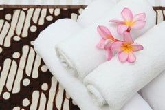 Détail fermé vers le haut des serviettes de fleurs sur le lit de couverture de batik photos stock