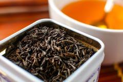 Détail sur la dose en métal blanc avec le thé de feuilles mobiles, et tasse brouillée image libre de droits