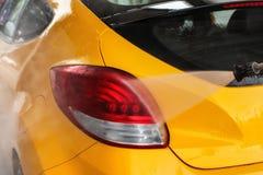 Détail sur la lumière arrière de voiture jaune étant lavée dans la lave-auto image libre de droits