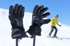 Détail sur les gants noirs de ski sur des poteaux de ski avec le skieur brouillé en Ba photographie stock libre de droits