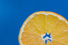 Détail sur une orange de tranche sur un fond bleu Photo libre de droits