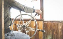 Détaillez étroit de la navigation de homme de barre et de la roue de contrôle de barre sur le voyage de rivière Images libres de droits