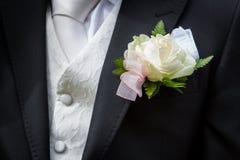 Détails blancs de fleur et de costume du boutonniere du marié Photographie stock libre de droits