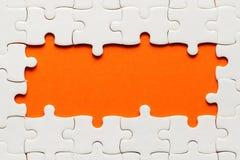 Détails blancs de puzzle sur le fond orange et d'endroit pour l'inscription photographie stock libre de droits