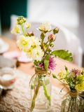 Détails d'une table rustique de mariage avec des écrous de camomiles et en bois images stock