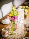 Détails d'une table rustique de mariage avec des écrous de camomiles et en bois photo stock