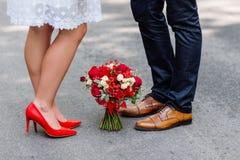 Détails de mariage : chaussures rouges et brunes élégantes des jeunes mariés Bouquet des roses se tenant au sol entre elles Nouve Image stock