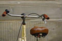 Détails de vieille bicyclette jaune siège en cuir avec les amortisseurs et la roue Images libres de droits
