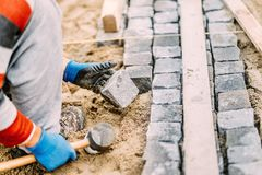 Détails des travaux de construction avec le travailleur industriel plaçant des blocs de pavé rond de granit sur le chemin ou l'al Photos stock