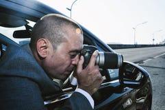 Détective ou paparazzi prenant des photos d'une voiture Photos libres de droits