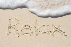 Détendez écrit en sable sur la plage Photos libres de droits
