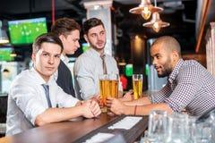 Détendez après travail Quatre amis buvant de la bière et ayant le toge d'amusement Photographie stock