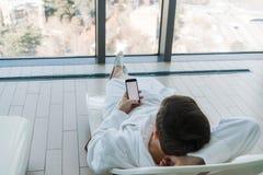 Détendez dans l'hôtel avec un téléphone à disposition Un homme se trouvant sur un canapé par la piscine et appréciant le smartpho image libre de droits