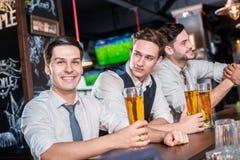 Détendez dans la barre après un dur labeur Le boire de quatre hommes d'amis soit Image stock