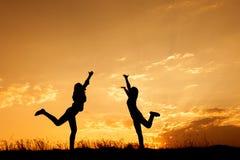 Détendez de deux femmes se tenant et de silhouette de coucher du soleil avec le spac de copie Images libres de droits