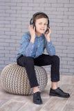 Détendez et concept de écoute de musique Suffisance européenne de garçon le peu Garçon dans la tenue de détente Photographie stock libre de droits