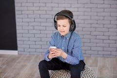 Détendez et concept de écoute de musique Suffisance européenne de garçon le peu Garçon dans la tenue de détente Photographie stock
