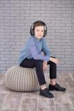 Détendez et concept de écoute de musique Suffisance européenne de garçon le peu Garçon dans la tenue de détente Photo libre de droits