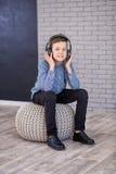 Détendez et concept de écoute de musique Suffisance européenne de garçon le peu Garçon dans la tenue de détente Photos stock
