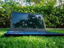 Détendez l'emplacement de travail de temps naturel avec l'ordinateur portable sur un champ d'herbe artificiel Photos libres de droits