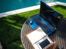 Détendez l'emplacement de travail de temps près de la piscine avec l'ordinateur portable, le carnet et le téléphone Photographie stock libre de droits