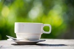 détendez la période, la tasse de café blanche avec le vert et le bok blured par jaune Images libres de droits