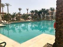 Détendez la piscine avec de l'eau bleu clair avec des lits pliants pour prendre un bain de soleil avec des parasols contre le con image libre de droits