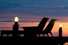 Détendez le bedson faisant le coin de plage un coucher du soleil de pont en bois Ombres abstraites de style Silhouette Photo stock