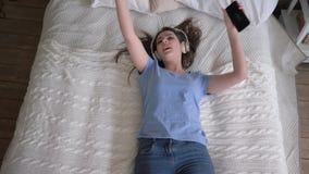 Détendez le temps, la fille joyeuse dans des écouteurs tombe sur le lit et écoute des chansons de smartphone et d'apprécier l banque de vidéos