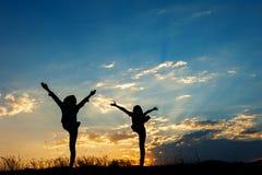 Détendez les femmes se tenant et la silhouette de coucher du soleil Image libre de droits