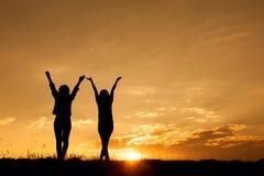 Détendez les femmes se tenant et la silhouette de coucher du soleil Image stock