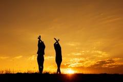 Détendez les femmes se tenant et la silhouette de coucher du soleil Photographie stock