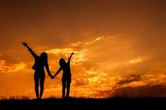 Détendez les femmes se tenant et la silhouette de coucher du soleil Photographie stock libre de droits