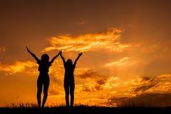 Détendez les femmes se tenant et la silhouette de coucher du soleil Photos stock