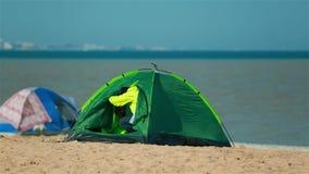 Détendez sur la plage dans une tente avec les enfants banque de vidéos