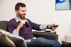 Détente à la maison avec de la bière et la TV Image stock