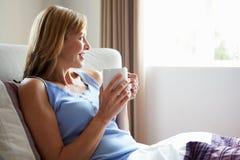 Détente âgée par milieu dans le lit avec la boisson chaude Photographie stock