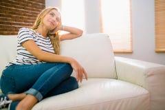 Détente assez blonde sur le divan photo libre de droits