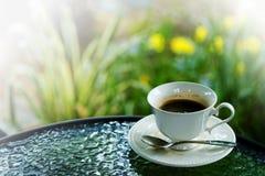 Détente avec le service noir chaud de café d'americano dans la tasse blanche dans le jardin Photos stock