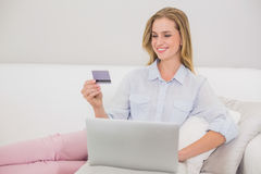 Détente blonde occasionnelle de sourire sur le divan faisant des achats en ligne images stock
