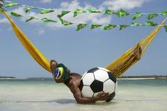 Détente brésilienne avec le football du football dans l'hamac de plage Images stock