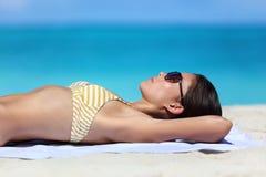 Détente de bronzage de femme de lunettes de soleil de plage dans le bikini Images stock