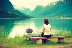 Détente de touristes de femme sur le bord de mer de fjord, Norvège images stock