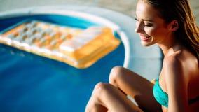 Détente et soleil de femme se bronzant par la piscine photo stock