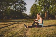 Détente extérieure Jeune femme s'asseyant en parc et musique de écoute sur son smartphone Photo libre de droits