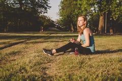 Détente extérieure Jeune femme s'asseyant en parc et musique de écoute sur son smartphone image stock
