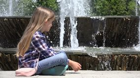 Détente se reposante d'enfant en parc par des baisses de observation de l'eau de fontaine, fille 4K extérieur banque de vidéos